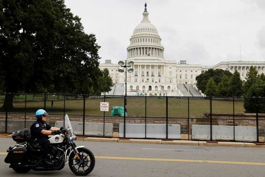 A US Capitol Police officer patrols the unscalable fence erected around the Capitol ahead of an expected rally Saturday in support of the Jan 6 defendants in Washington, US September 17, 2021. REUTERS/Jonathan Ernst
