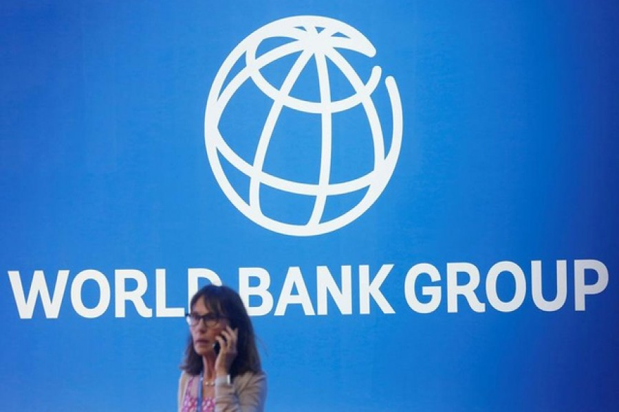 A participant stands near a logo of World Bank at the International Monetary Fund - World Bank Annual Meeting 2018 in Nusa Dua, Bali, Indonesia, October 12, 2018 — Reuters