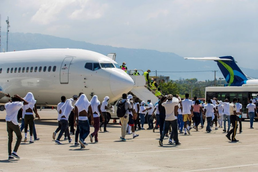 Haitian migrants board an airport bus aftter US authorities flew them out of a Texas border city after crossing the Rio Grande river from Mexico, at Toussaint Louverture International Airport in Port-au-Prince, Haiti September 21, 2021. REUTERS/Ralph Tedy Erol