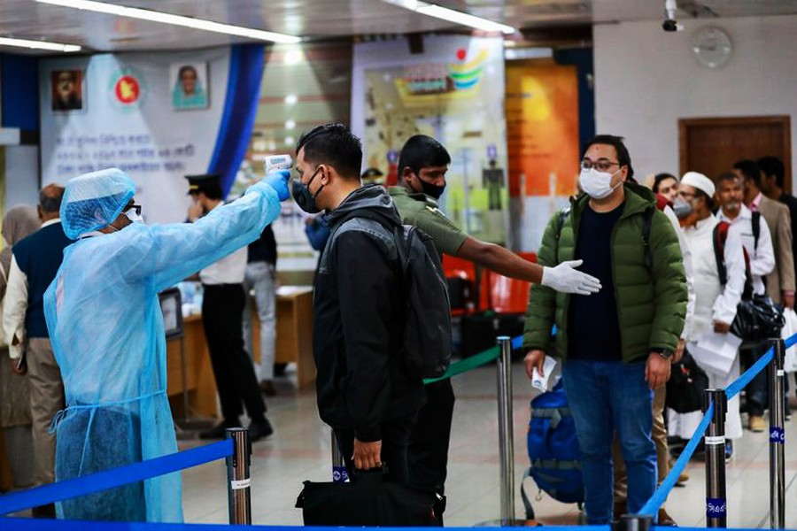 Passengers are checked with a thermal scanner at the Hazrat Shahjalal International Airport in Dhaka, Bangladesh, March 11, 2020. Reuters