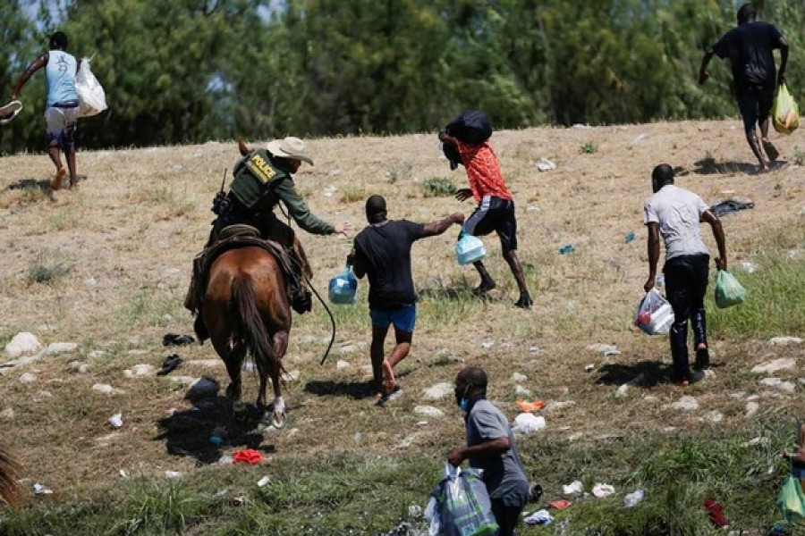 A US law enforcement officer on horseback chases migrants returning to the United States after buying food in Mexico, as seen from Ciudad Acuna, Mexico September 19, 2021. Reuters