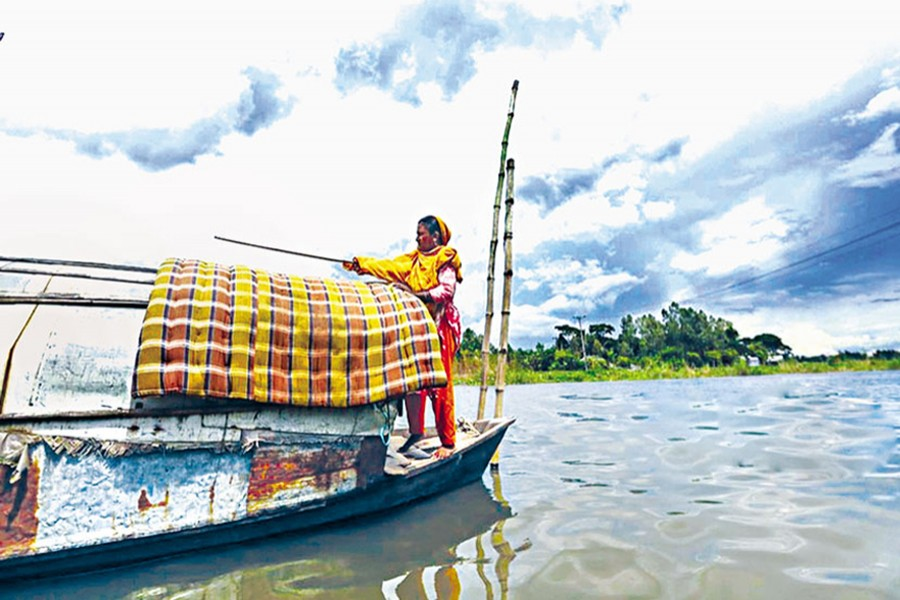 Anjuman Begum, a water gypsy, is placing a mattress over the rooftop of their boat for drying in the sun— bdnews24.com