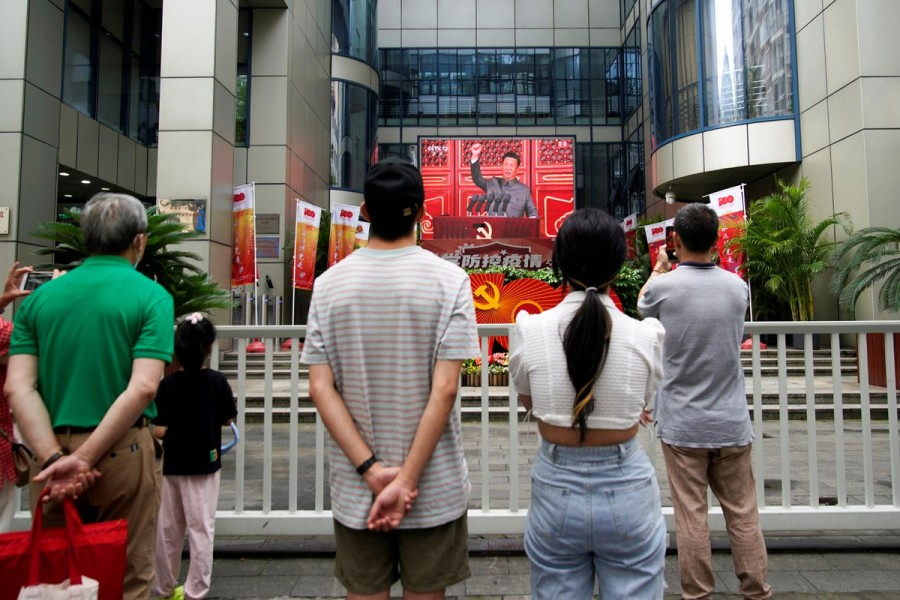 People watch a giant screen broadcasting Chinese President Xi Jinping's speech at a celebration marking the 100th founding anniversary of the Communist Party of China, in Shanghai July 1, 2021. REUTERS/Aly Song