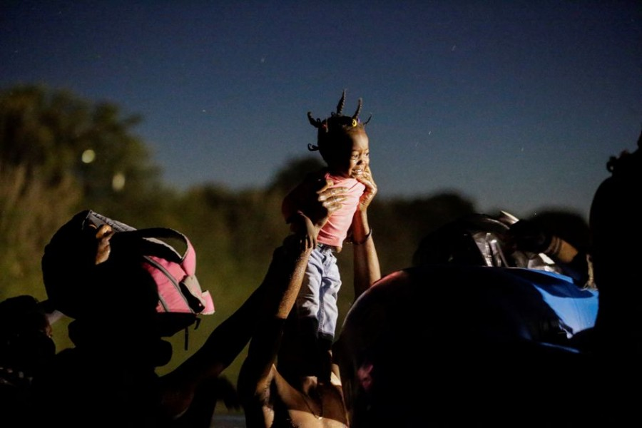 Migrants seeking refuge in the US and crossing the Rio Grande river towards Del Rio, Texas, US, hold up a girl to be helped by Border Patrol Agents on an inflatable boat, as seen from Ciudad Acuna, Mexico, September 23, 2021. REUTERS/Daniel Becerril