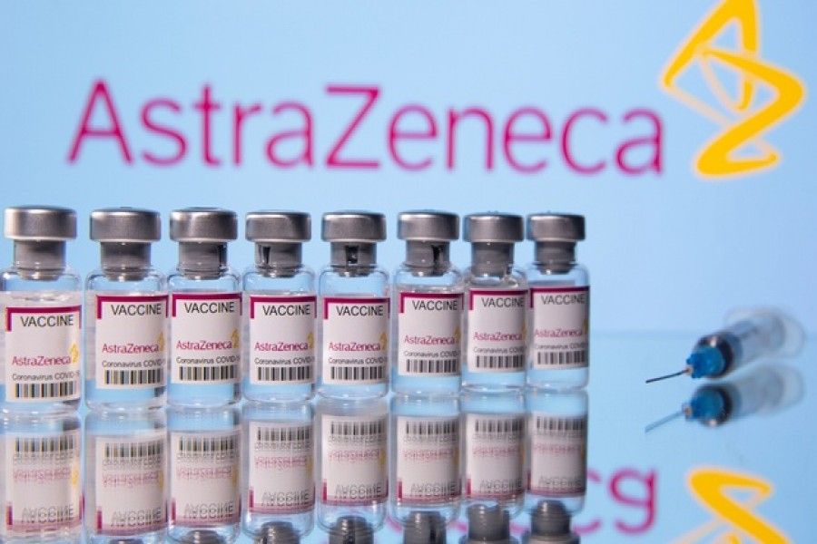 """Vials labelled """"Astra Zeneca Covid-19 Coronavirus Vaccine"""" and a syringe are seen in front of a displayed AstraZeneca logo, in this illustration photo taken March 14, 2021 -- Reuters/Files"""