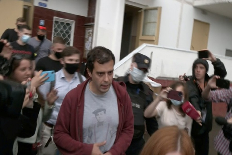 """Roman Dobrokhotov, the editor-in-chief of """"The Insider"""" Russian news outlet, who was taken in by Interior Ministry officers for questioning over a slander case, is escorted to a police van in Moscow, Russia July 28, 2021, in this still image taken from video. Video taken July 28, 2021. REUTERS TV/via REUTERS"""