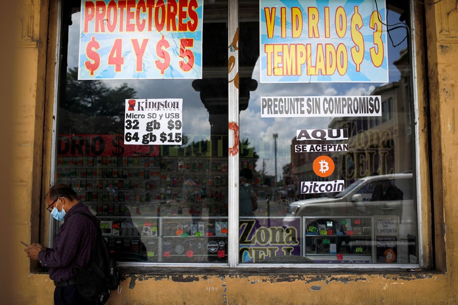 """A man stands by a sign that reads, """"Bitcoin accepted here"""", outside a store where the cryptocurrency is accepted as a payment method in San Salvador, El Salvador on September 24, 2021 — Reuters photo"""