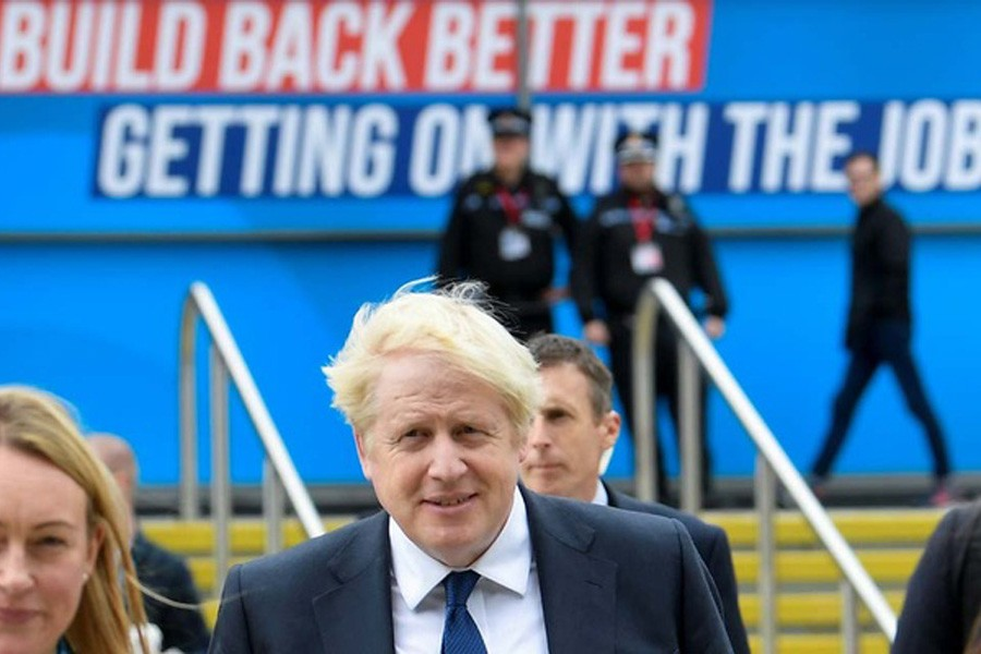 Britain's Prime Minister Boris Johnson walks through the Conservative Party annual conference venue, in Manchester, Britain, October 3, 2021. Reuters