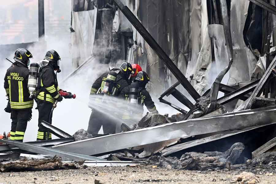 Firefighters working at the spot where a small plane crashed into a building in Italy on Sunday –Reuters photo