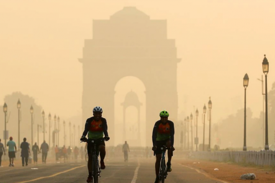 Men ride their bicycles in front of the India Gate shrouded in smog, in New Delhi, India, October 24, 2020. REUTERS/Adnan Abidi