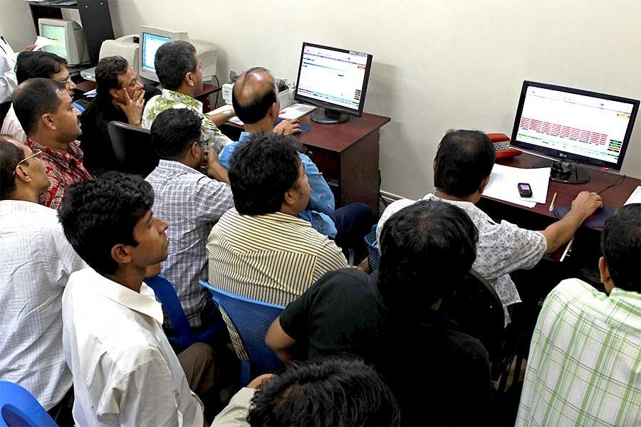 Investors monitoring stock price movements on computer screens at a brokerage house in the capital city — FE/Files