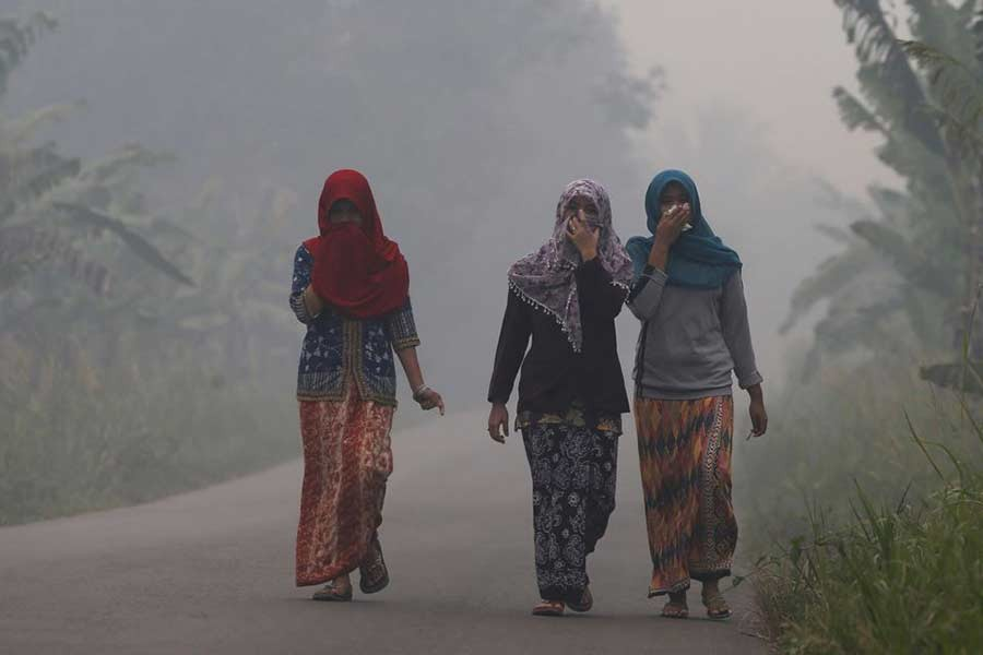 Villagers walking on a street as the haze shrouds Pulau Mentaro village in Muaro Jambi, on the Indonesian island of Sumatra, on September 15 in 2015 –Reuters file photo