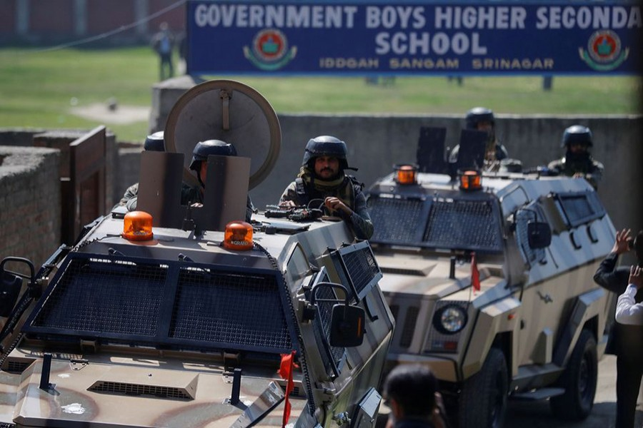 Indian security forces keep guard atop armoured vehicles, outside a government school after suspected militants shot and killed two teachers in Srinagar on October 7, 2021 — Reuters photo