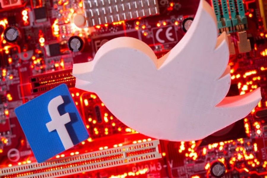 3D printed Facebook and Twitter logos are placed on a computer motherboard in this illustration taken January 21, 2021 – Reuters/Files