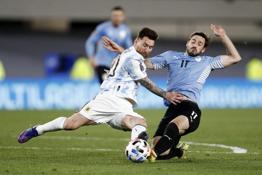 Soccer Football - World Cup - South American Qualifiers - Argentina v Uruguay - El Monumental, Buenos Aires, Argentina - October 10, 2021 Argentina's Lionel Messi in action with Uruguay's Matias Vina REUTERS/Agustin Marcarian