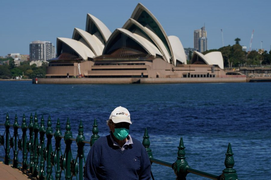 A person in protective face mask walks along the harbour waterfront across from the Sydney Opera House during a lockdown to curb the spread of coronavirus disease (Covid-19) outbreak in Sydney, Australia on October 6, 2021 — Reuters/Files