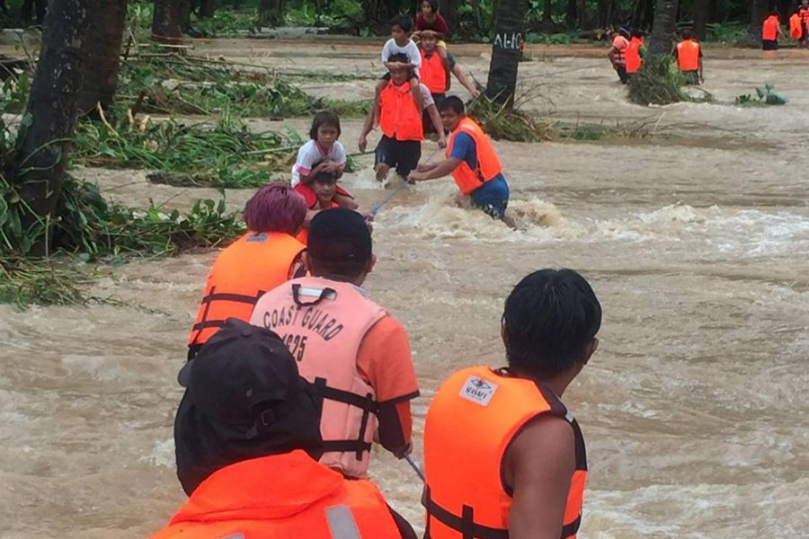 People cross floodwaters caused by tropical cyclone Kompasu during an evacuation assisted by the Philippine Coast Guard (PCG) at Brooke's Point, Palawan, in the Philippines on Ocotober 12, 2021, in this image obtained via social media — Philippine Coast Guard via REUTERS