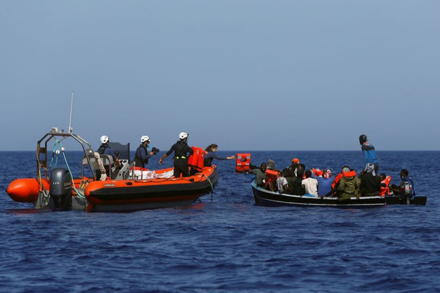 Rigid-hulled inflatable boat (RHIB) crew members from the German NGO migrant rescue ship Sea-Watch 3 distribute life jackets to migrants in a small wooden boat in international waters off the coast of Libya, in the western Mediterranean Sea on August 1, 2021 — Reuters/Files