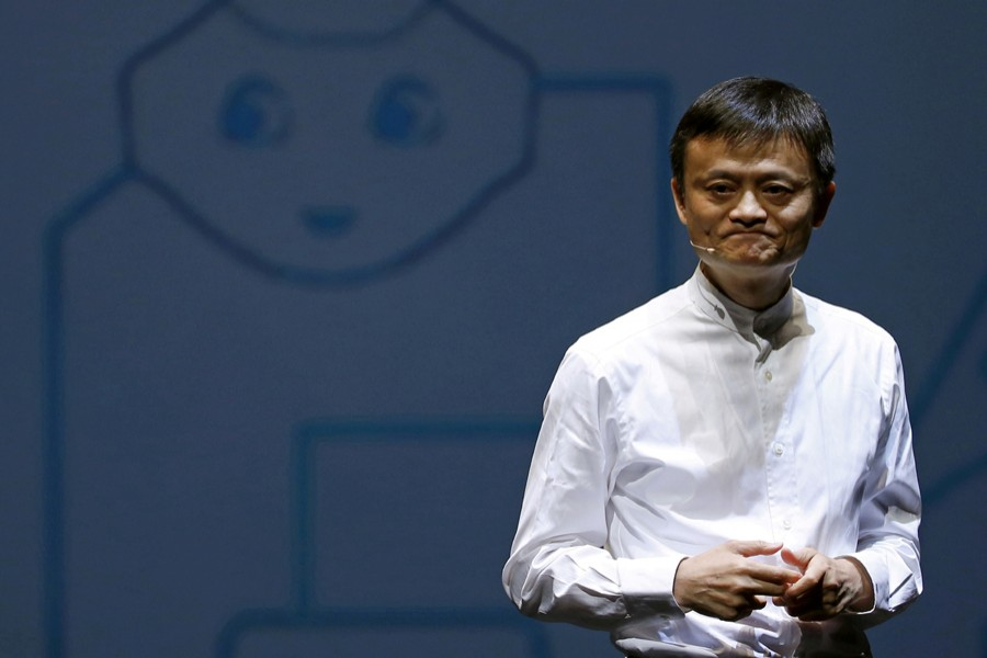Jack Ma, founder and executive chairman of China's Alibaba Group, speaks in front of a picture of SoftBank's human-like robot named 'pepper' during a news conference in Chiba, Japan on June 18, 2015 — Reuters/Files
