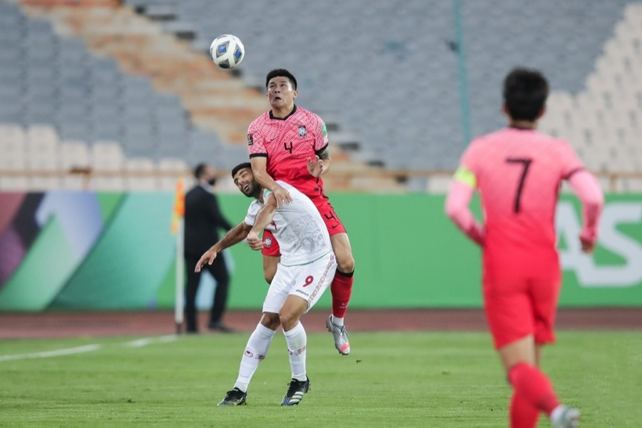 Kim Min-jae of South Korea (cntre) battles with Mehdi Taremi of Iran for the ball during the teams' Group A match in the final Asian qualifying round for the 2022 FIFA World Cup at Azadi Stadium in Tehran on October 12, 2021, in this photo provided by the Korea Football Association — via Yonhap News Agency