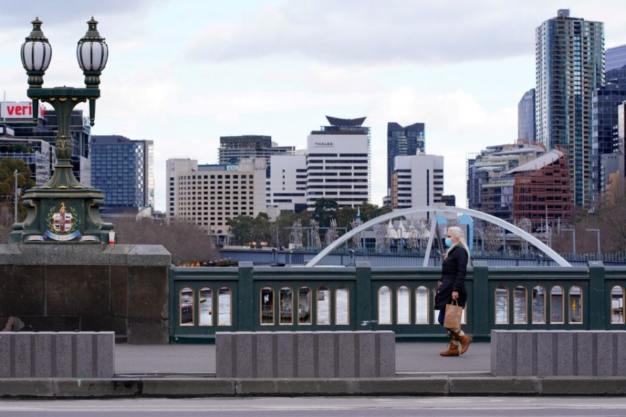 A lone woman, wearing a protective face mask, walks across a city centre bridge as the state of Victoria looks to curb the spread of a coronavirus disease (Covid-19) outbreak in Melbourne, Australia on July 16, 2021 — Reuters/Files