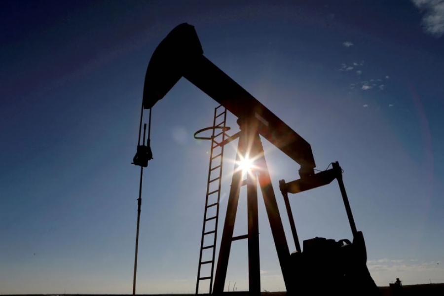 The sun is seen behind a crude oil pump jack in the Permian Basin in Loving County, Texas, US, November 22, 2019. REUTERS/Angus Mordant/File Photo