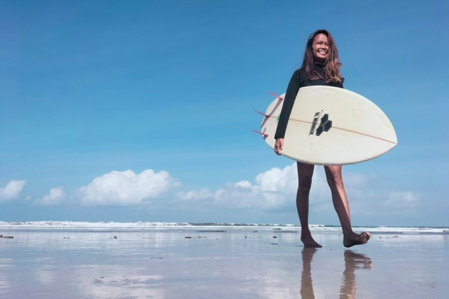 A surfing business owner, 38-year-old, Halfia Lando poses holding a surfboard at a Kuta beach as Indonesia opens up the tourist island of Bali to some countries including China, New Zealand, and Japan from Oct 14, visitors are still required to quarantine for eight days at their own expense, in Denpasar, Bali, Indonesia, Oct 12, 2021. REUTERS/Sultan Anshori